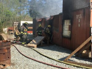 Firefighters in bunker gear and yellow helmets enter a rust red shipping container. Smoke billows from the rear of the container. It is a training prop.