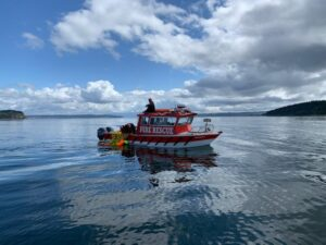 A red Camano Fire boat on the water, with blue sky and clouds above. People in blue fire uniforms are on the boat.
