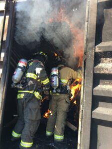 two firefighters in black and tan bunker gear walk into smoke and fire
