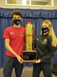 a teenage male in red shirt and teenage female in navy blue sweatshirt hold a fire extinguisher trophy