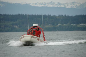 a white fire department boat on the water, with mountains in the background