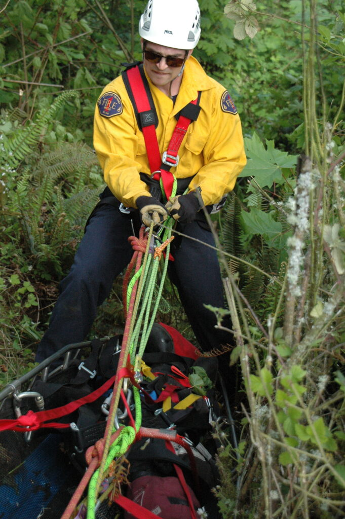 a firefighter in helmet uses ropes to bring a litter up over the edge of a cliff