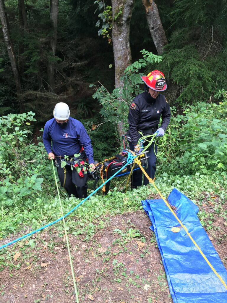 Two firefighters in helmets use ropes to bring a litter up over the edge of a ravine